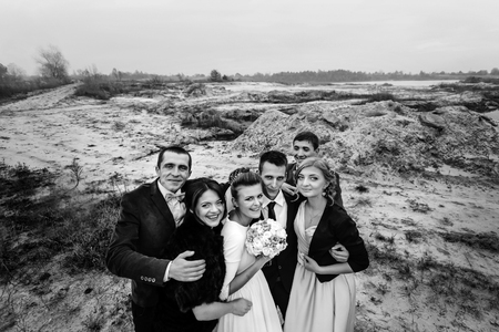 bride and groom with happy groomsmen and bridesmaids having fun and laughing at sandy lake, luxury wedding Stock Photo
