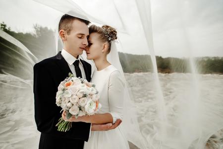 bride and groom hugging with tender under veil, luxury elegant wedding walk Stock Photo