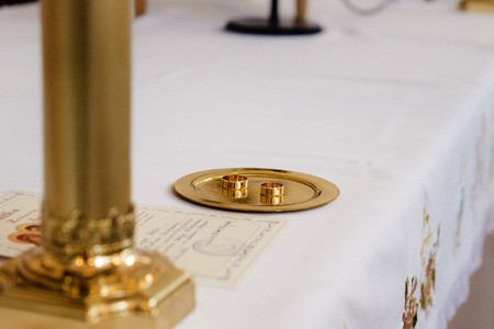 elegant luxury golden wedding rings on plate in church
