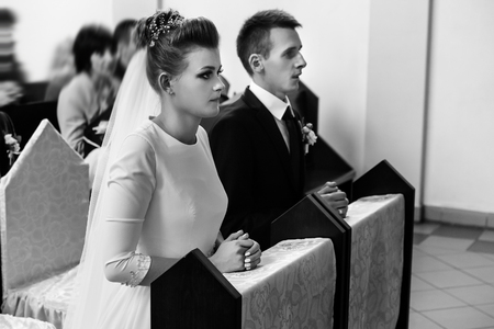 bride and groom preparing for communion on knees at wedding ceremony in church