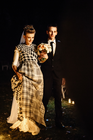 gorgeous bride and stylish groom at evening wedding ceremony walking down with candles, luxury  reception in restaurant
