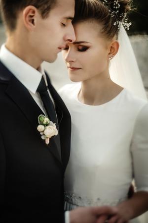 gorgeous bride and stylish groom gently hugging at sandy beach lake, beautiful moment, luxury wedding Stock Photo