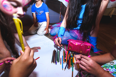 multiple: group of  kids drawing with colorful pencils and having fun at birthday celebration in restaurant Stock Photo