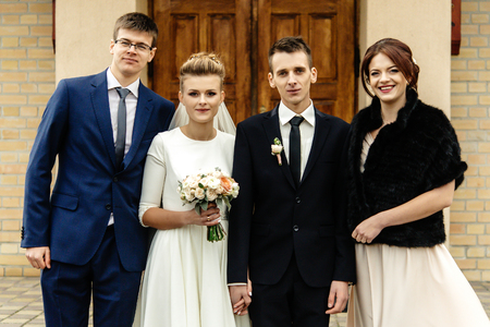 bride and groom with happy groomsman and bridesmaid posing at church after luxury wedding ceremony