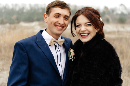 happy groomsman and bridesmaid having fun and laughing at sandy lake, luxury wedding