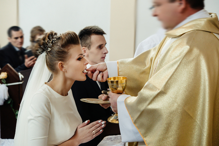 bride and groom having communion with priest on knees at wedding ceremony in church Standard-Bild