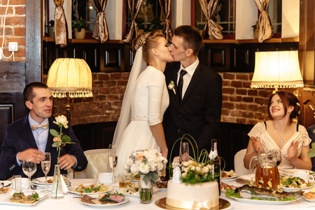 happy bride and groom kissing at their table,  gorgeous wedding reception