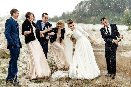 bride and groom with happy groomsmen and bridesmaids having fun and popping champagne, luxury wedding celebration, hilarious moment