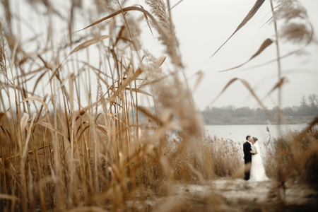 gorgeous bride and stylish groom gently hugging at  beach lake in evening, beautiful tender moment, unusual view Stock Photo