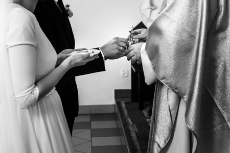 hands of bride and groom preparing for communion at wedding ceremony in church Stock Photo