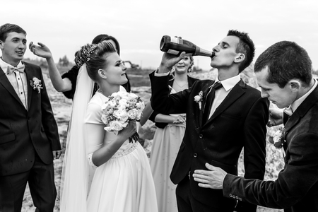 bride and groom with happy groomsmen and bridesmaids having fun and toasting with champagne, black and white, hilarious moment