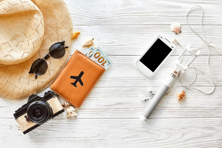 summer travel vacation concept flat lay, space for text. selfie stick phone camera passport money plane hat and sunglasses and shells on white wooden background top view. hello summer. Reklamní fotografie
