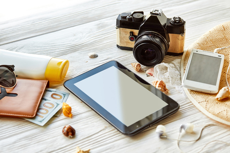 summer travel vacation concept, space for text. empty tablet screen, camera sunglasses passport money phone hat shells on white wooden table. wanderlust, summer holiday Banque d'images
