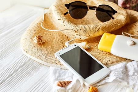 夏の旅行休暇のコンセプト、テキストのためのスペース。白い木製の背景に空の画面とサングラスと日焼け止めの殻帽子を持つ携帯電話。こんにち