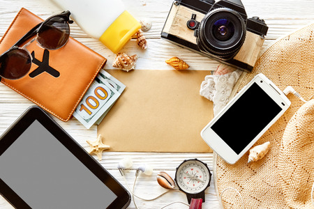 summer travel planning vacation concept, space for text, flat lay. empty tablet screen  card, camera sunglasses compass passport money phone hat shells on white wooden background top view