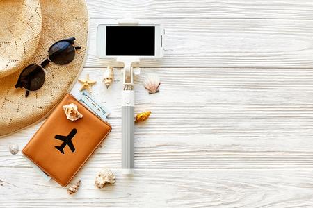 zomer reizen vakantie concept plat leggen, ruimte voor tekst. selfie stick telefoon camera paspoort vliegtuig vliegtuig hoed en schaduwen op witte houten achtergrond. Hallo zomer. reislust. spaar momenten Stockfoto