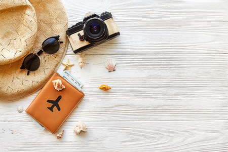 夏旅行休暇の概念フラット レイアウト、テキストのためのスペース。写真カメラ パスポートお金面帽子とサングラスと白い木製の背景の上にシェル
