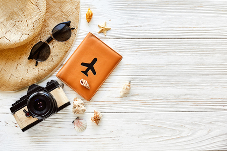 summer travel vacation concept flat lay, space for text. photo camera passport plane hat  and sunglasses and shells on white wooden background top view. hello summer. wanderlust Archivio Fotografico