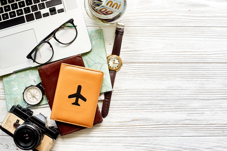 travel and wanderlust concept, planning summer vacation background flat lay, space for text. map compass photo camera glasses wallet money watch laptop on white wooden table top view