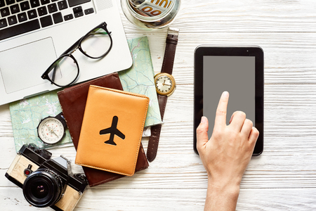 planning summer vacation flat lay, space for text. hand pointing on tablet with empty screen, money map compass camera glasses wallet laptop on wooden background. time to travel wanderlust Stock Photo