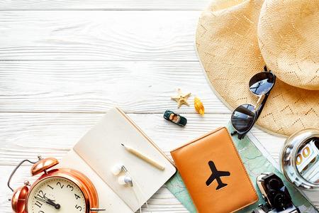 Tiempo para viajar concepto, espacio para texto. traza el teléfono del dinero del pasaporte de la cámara con las gafas de sol y el juguete vacíos del coche de las cáscaras del sombrero del reloj en el fondo de madera blanco. hola vacaciones, planeando vacaciones Foto de archivo - 77213704
