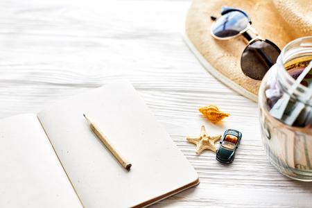 planning zomer reizen concept en reislust, ruimte voor tekst. zeester en autostuk speelgoed, leeg notitieboekje met de hoed van de de kruikzonnebril van het pengeld zonnebril op witte houten achtergrond. hallo vakantie vakantie
