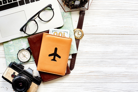 travel and wanderlust concept, planning summer vacation background flat lay, space for text. map compass photo camera glasses wallet watch laptop on white wooden table top view