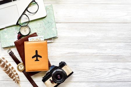 Reise- und Fernwehkonzept, planende Sommerferienhintergrund-Ebenenlage, Raum für Text. Karte Kompass Foto Kamera Sonnenbrille Brieftasche Uhr Laptop auf weißem Holztisch Draufsicht Standard-Bild
