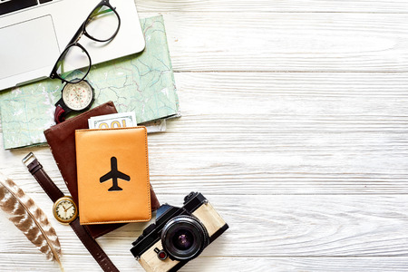 travel and wanderlust concept, planning summer vacation background flat lay, space for text. map compass photo camera sunglasses wallet watch laptop on white wooden table top view