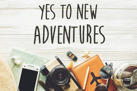new adventure text sign concept. say yes to new adventures. time to travel, wanderlust background flat lay. camera sunglasses passport money map phone hat car plane  on white wooden table top view