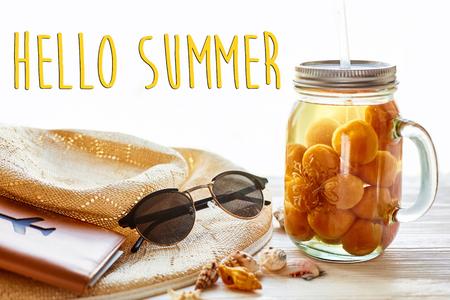 黄色のカクテル ジュース アプリコット、帽子、サングラス、白い素朴な木製の背景光の中で貝殻のハロー夏テキスト。テキストのためのスペース。