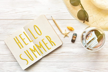 HI: hello summer text, planning summer travel concept and wanderlust flat lay, space for text. empty notebook with pen money jar sunglasses hat shells car toy on white wooden background.