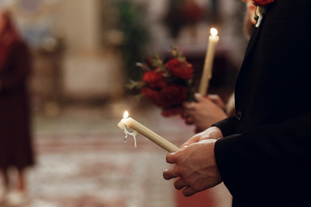 stylish bride and groom holding candles in hands at wedding ceremony in church. spiritual couple. space for text