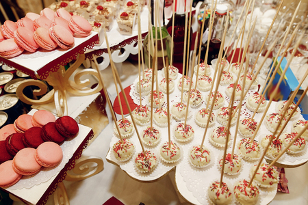 delicious white pops with icing at candy bar with sweets and drinks at luxury wedding reception. catering at restaurant. space for text