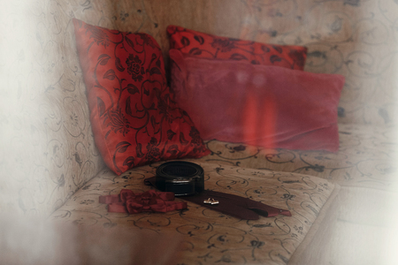 cuff link: stylish red bow-tie and tie with belt and cufflinks on bed. morning preparation for wedding. groom getting ready in hotel room.