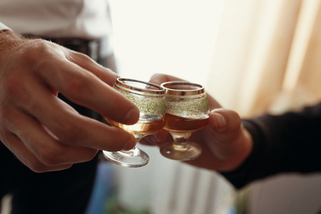 hands of man holding glasses with vodka and toasting. group of men cheering and clinking with drinks at wedding reception Stock Photo