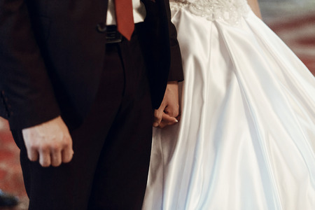 stylish bride and groom holding hands at wedding ceremony in church. spiritual couple. space for text
