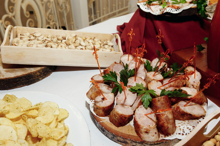 wedding feast: salty smoked sausage and chips nuts on wooden desk on table, wedding reception. beer bar and snacks. catering in restaurant Stock Photo