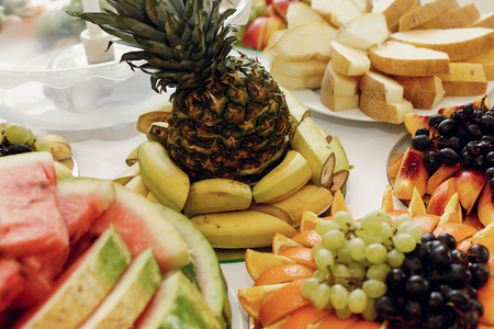 wedding feast: delicious pineapple and bananas, grapes and oranges, fruit bar table at wedding reception. catering in restaurant