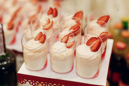 stylish desserts with strawberry, candy bar with sweets at luxury wedding reception. catering at restaurant. cupcakes  macaroons on table. space for text