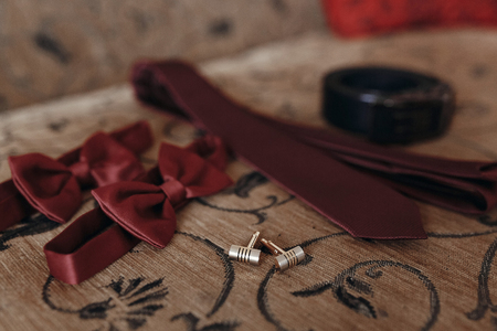 stylish red bow-tie and tie with belt and cufflinks on bed. morning preparation for wedding. groom getting ready in hotel room.