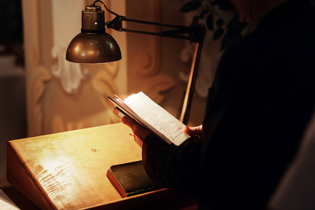 priest holding holy bible book and reading at wedding ceremony. spiritual moment in church in light. space for text Stock Photo