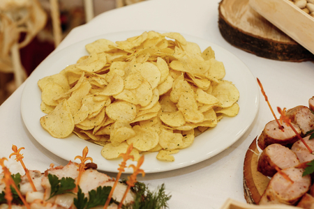 salty chips and nuts on wooden desk on table, wedding reception. beer bar and snacks. catering in restaurant