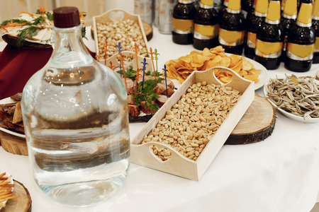 salty chips and nuts and vodka on wooden desk on table, wedding reception. beer bar and snacks. catering in restaurant