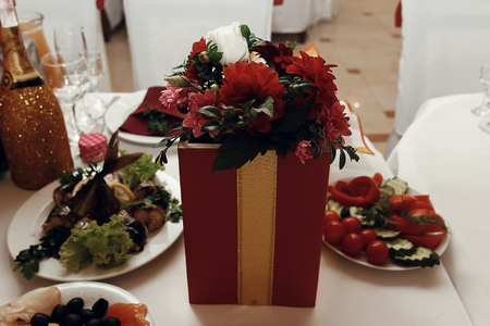 stylish red vase with flowers on table, luxury decorated place for wedding ceremony and reception