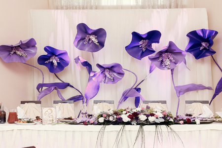 big purple flowers at wedding centerpiece for bride groom setting in restaurant, luxury wedding reception, stylish decor