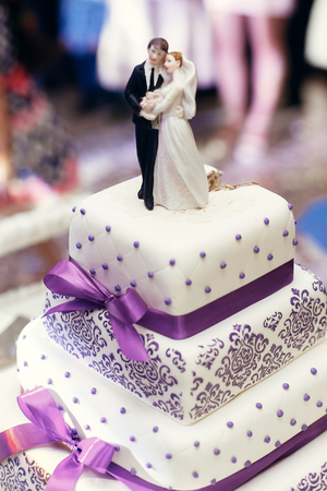 bride and groom on wedding cake. figurines on cake top with purple icing, luxury wedding reception, catering in restaurant