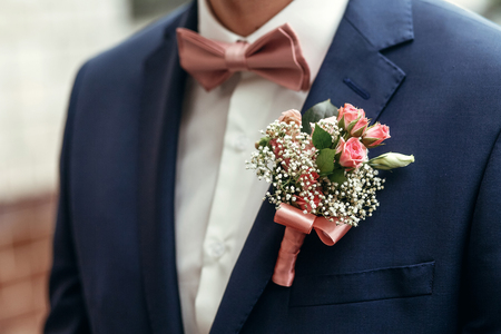 stylish groom or groomsmen in suit with pink roses boutonniere and bow tie posing, getting ready in morning for wedding ceremony Stock Photo