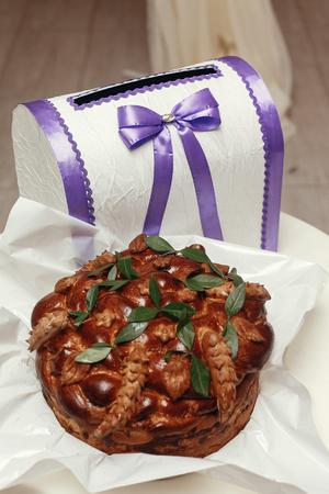 Boîte cadeau invité et gâteau traditionnel à l'arc au restaurant, réception de mariage de luxe, décor élégant Banque d'images - 77683490