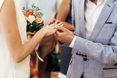 bride with bouquet and groom exchanging wedding rings at wedding registry. stylish couple official wedding ceremony Stock Photo